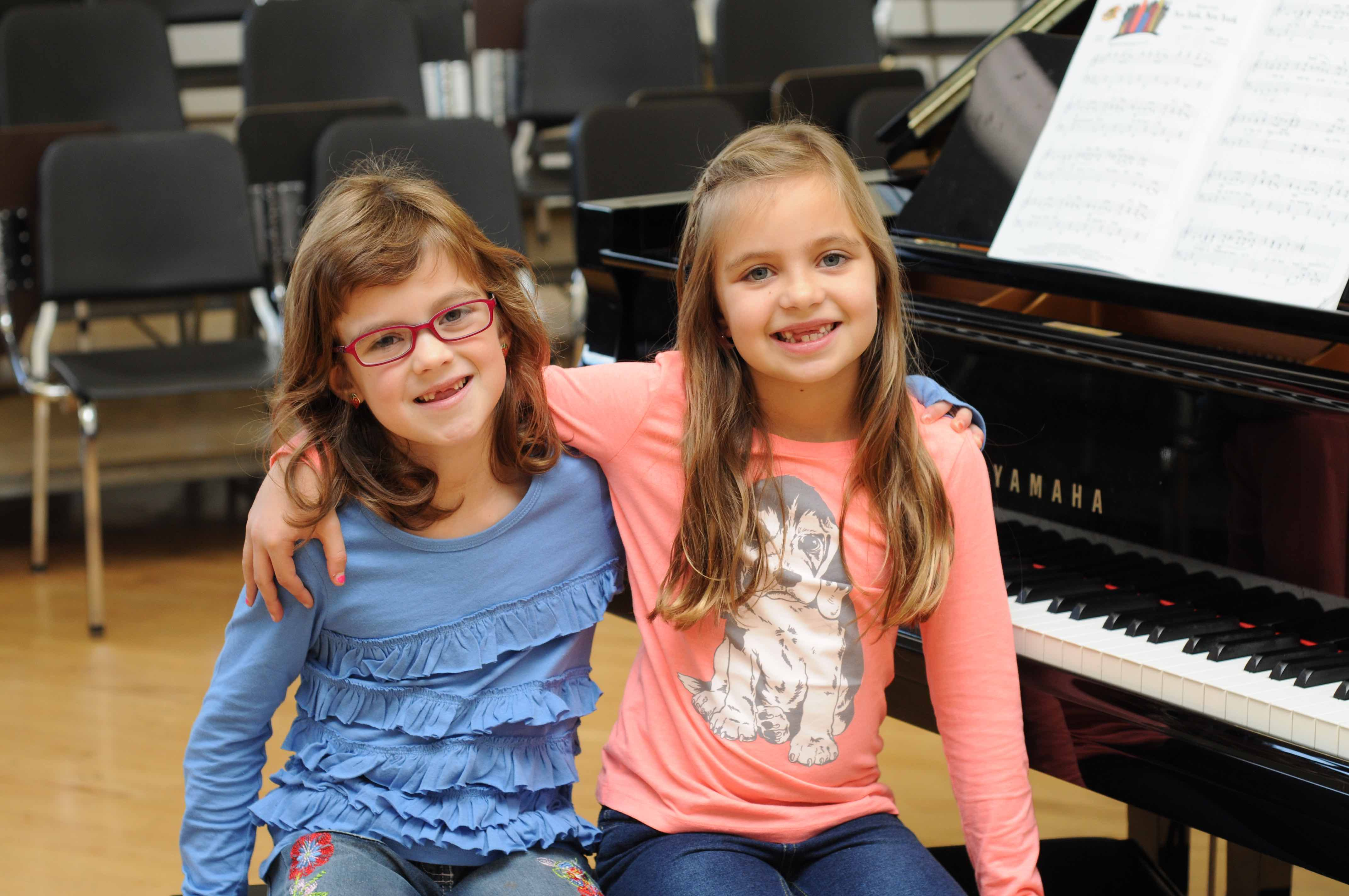 Eva and Demi sitting by the piano